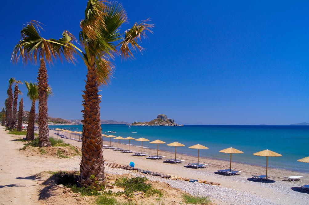 Strand in der Kéfalos Bucht mit Palmen, Liegen und Sonnenschirmen