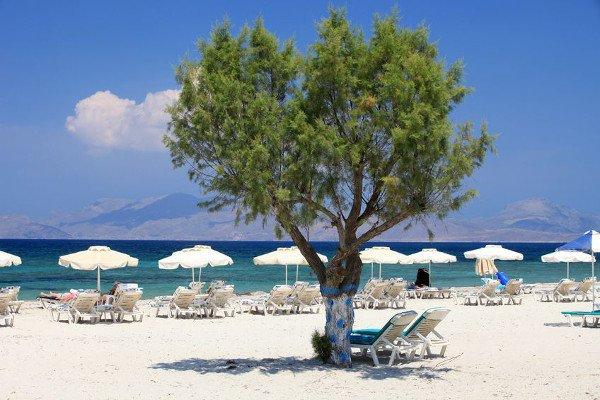 Strand von Mastichári mit Liegen und Sonnenschirmen für Badeurlauber
